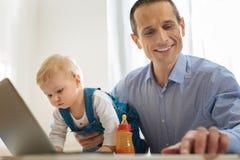 Notes heureuses de lecture de jeune homme tandis que son bébé explorant un ordinateur portable moderne Photographie stock