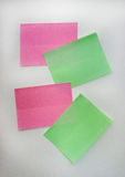 Notes -like colored green and pink sticky notes stick to a white wall Stock Photography