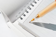 Notes making. An orange mechanical pencil writing on a spiral notebook royalty free stock image