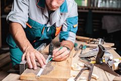 Notes masculines de charpentier avec le crayon utilisant la bande de mesure sur le conseil, marques pour la coupe de scie, mains  photographie stock libre de droits