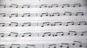 Notes musicales écrites sur les lignes d'écriture Image stock