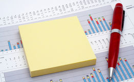 Notes and pen on earnings chart Royalty Free Stock Image