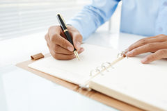 Notes in personal organizer. Close-up of male hand making notes in organizer Stock Image
