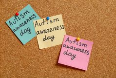 Notes with phrase. `Autism awareness day` on cork background Royalty Free Stock Images