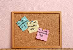 Notes with phrase. `Autism awareness day` on cork board against color background Stock Photography