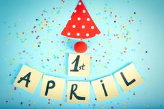 Notes with phrase. `1st April`, clown nose and party cap on color background. Fool`s day celebration Royalty Free Stock Images