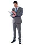 Notes réussies d'écriture d'homme d'affaires sur la planchette image stock