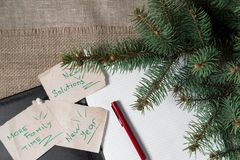 Notes reminders and goals, a business notebook, on the next new year background with Christmas fir branches. Notes reminders and goals for the next new year on Stock Photography