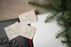 Notes reminders and goals, a business notebook, on the next new year background with Christmas fir branches. Notes reminders and goals for the next new year on Royalty Free Stock Image