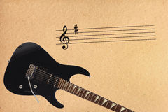 Notes stave and black electric rock guitar at the bottom of rough cardboard background. Stock Photos