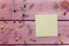 Notes, sticker, paper clips. Clips are on the wooden table royalty free stock image