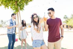 Nothing Beats Good Company. Hispanic couple smiling while clinking beer glasses at outdoor party stock photography