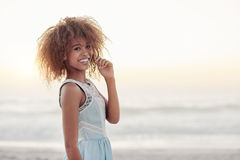 Nothing beats sunset at the beach. Portrait of a beautiful young woman standing on a beach at sunset stock image