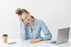 Nothing can be done to fix problem. Unhappy devestated female entrepreneur in glasses, crying, clenching teeth and. Touching forehead, looking upset at table Stock Photos