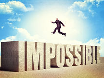 Nothing is impossible. Man jump over impossible concrete word royalty free stock image