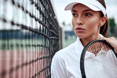 Nothing is impossible. Portrait of young beautiful tennis player with a racket on a court, looking away. royalty free stock photo