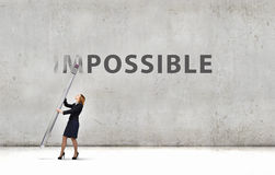 Nothing is impossible. Young businesswoman with huge pencil changing word impossible royalty free stock image