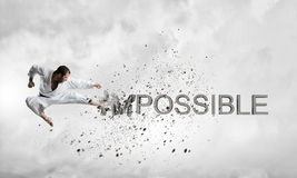 Nothing is impossible. Young determined karate man breaking stone impossible word stock image