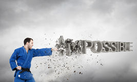Nothing is impossible. Young determined karate man breaking stone impossible word stock photography