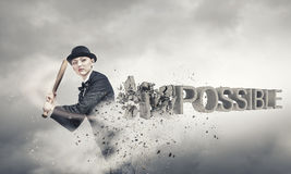 Nothing is impossible. Young woman crashing word impossible with baseball bat stock photography