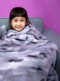 Nothing like a Warm Comfortable Blanket. Smiling Child with a Warm Blanket on a Sofa Stock Photography