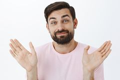 Nothing to be done, cannot help. Shgging careless and unbothered carefree bearded guy raising palms in indifferent and. Uninterested gesture smirking being royalty free stock images