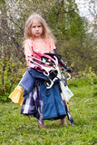 Nothing to wear. Sad little girl standing with heap of dresses in her hands Royalty Free Stock Photography