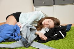 Dissatisfied teenage girl lying on the floor in the chaos  of  her outfit. Nothing to wear. Teenage girl lying  on the floor churns frustrated her clothes royalty free stock image
