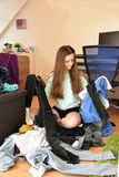 Frustrated teenage girl choosing her outfit. Nothing to wear. Teenage girl sits on the floor in the chaos of her clothes, looking frustrated royalty free stock photo
