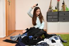 Frustrated teenage girl choosing her outfit royalty free stock photography