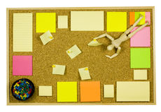 Notice board. Cork notice board with colorful sticky post-it notes and a wooden model dummy doll Stock Photos