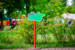 Notice board, green blank plate for text in the park on natural background. Stock Image