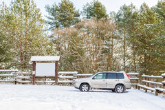 Notice board otdoor and car. Notice board otdoor at winter time, trees with snow suv car Royalty Free Stock Image