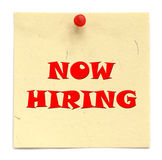 Notice inscribed NOW HIRING. Over white background Stock Photos