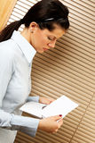 Notice of layoff. Woman as office worker is reading notice of layoff stock photo
