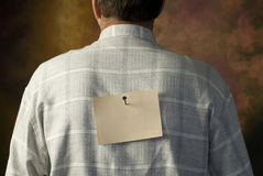 Notice nailed to man's back Stock Photography