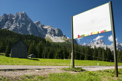 Notice on road with mountains. Empty road sign nearby the street with stunning mountain landscape in a sunny day - Italy 2009 - Dolomiti Royalty Free Stock Images