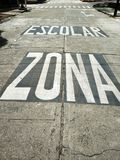 Notice of school zone on the road in spanish. Roadway marking indicating this part of the road is near a school zone Stock Images