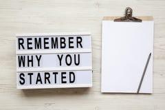 Noticeboard, het potlood en ` herinneren waarom u `-woorden op lightbox over witte houten achtergrond, van hierboven begon stock afbeelding