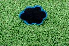 Noticeboard met kader op groen kleurenzand stock foto