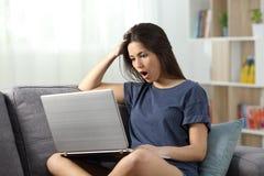 Noticias adolescentes chocadas de la lectura en línea en un ordenador portátil en casa Foto de archivo