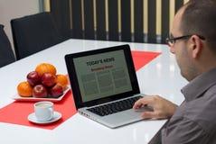 Noticias de última hora de la lectura del hombre en un ordenador portátil Foto de archivo libre de regalías