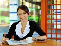 Noticias de la lectura de la mujer en el café Imagenes de archivo