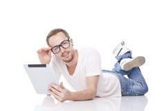 Noticias de la lectura del hombre en el ordenador de la tablilla Foto de archivo libre de regalías
