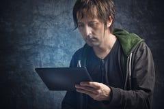 Noticias de la lectura del hombre en la tableta de Digitaces Fotografía de archivo libre de regalías
