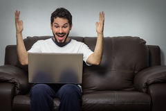 Noticias de lectura del hombre buenas en su ordenador portátil imágenes de archivo libres de regalías