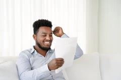 Noticias de lectura del hombre feliz del empresario buenas en una letra en el sofá en hogar imagen de archivo