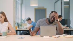 Noticias de lectura del hombre joven malas en el ordenador portátil en oficina Persona africana chocada almacen de video