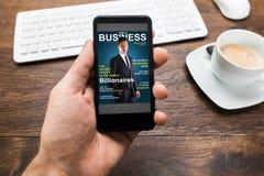 Noticias de negocio de demostración de Person Hands With Mobile Phone Foto de archivo libre de regalías