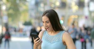 Noticias emocionadas de la lectura de la mujer en un teléfono en la calle almacen de metraje de vídeo